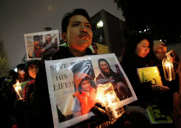 People holding placards take part in a vigil in front of Prime Minister Shinzo Abe's official residence in Tokyo, January 30, 2015