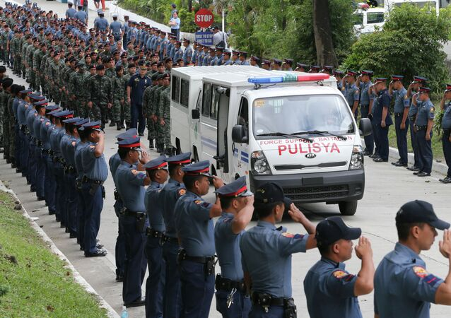 Philippine National Police salute for the final sendoff as a van with one of the remains of 44 special commandos leaves Camp Bagong Diwa for its final journey to his hometown Saturday, Jan. 31, 2015 at suburban Taguig city, south of Manila, Philippines