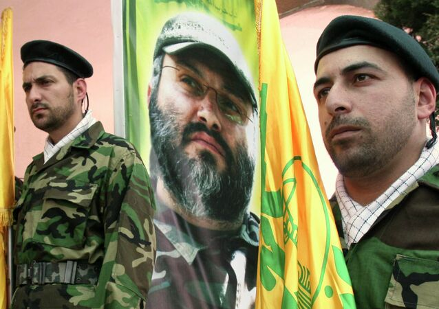 Hezbollah members stand guard in front of a picture of assassinated Hezbollah top commander Imad Imad Mughniyah
