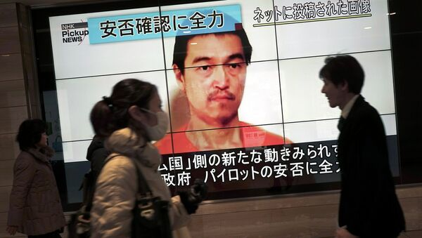 People walk by a screen showing TV news reports of Japanese hostage Kenji Goto, held by the Islamic State group, in Tokyo Saturday, Jan. 31, 2015 - Sputnik International