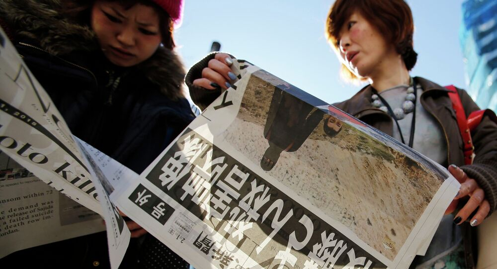 Women read an extra edition of a newspaper, which reported that Islamic State militants said they had beheaded Japanese journalist Kenji Goto, in Tokyo's Ginza district February 1, 2015