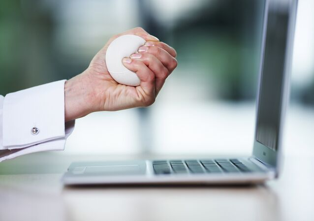 Business woman squeezing stress ball over desk, close-up
