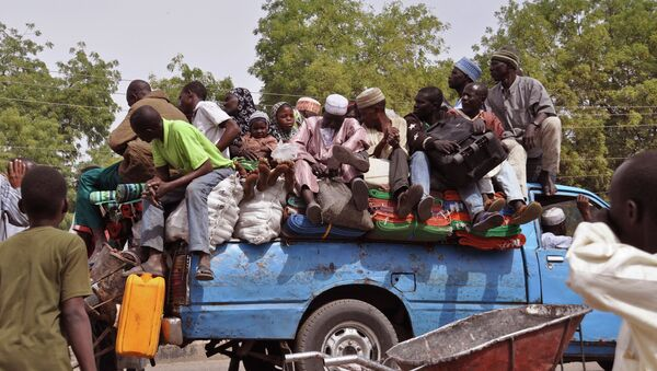 Villagers sit on the back of a small truck as they and others flee the recent violence near the city of Maiduguri, Nigeria - Sputnik International