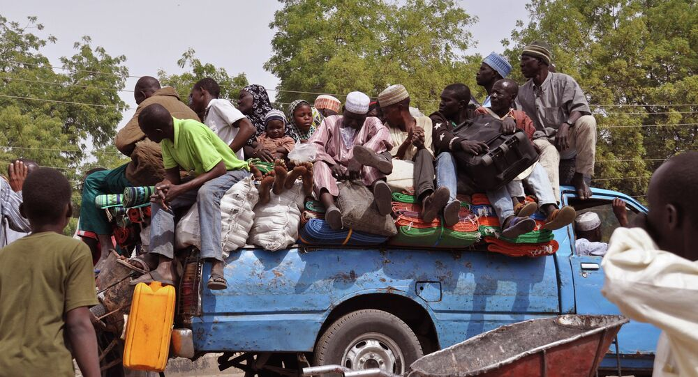 Villagers sit on the back of a small truck as they and others flee the recent violence near the city of Maiduguri, Nigeria