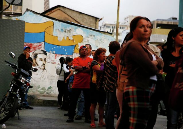 People line up to buy toilet paper at a supermarket in downtown Caracas January 19, 2015