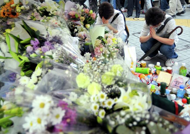 Two men offer prayer for victims of the 2008 knifing rampage in which seven people were stabbed to death at Tokyo's Akihabara shopping district