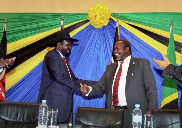 South Sudan's President Salva Kiir, left, shakes hands with rebel leader and former vice president Riek Machar