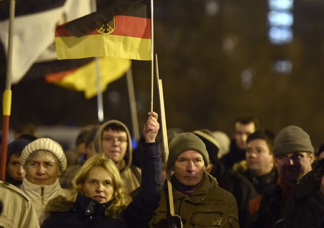 Anti-Islam protesters hold German flags during a BERGIDA rally, a local copycat of Dresden's right-wing populist movement PEGIDA (Patriotic Europeans Against the Islamisation of the Occident), at Alexander Platz in Berlin, eastern Germany