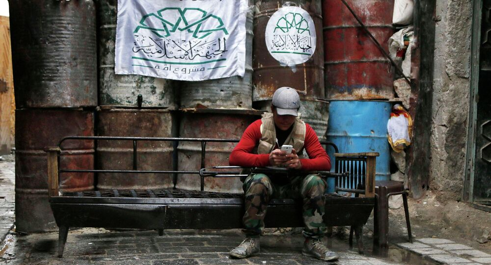 A rebel fighter uses his mobile phone beside barriers at a frontline in Old Aleppo