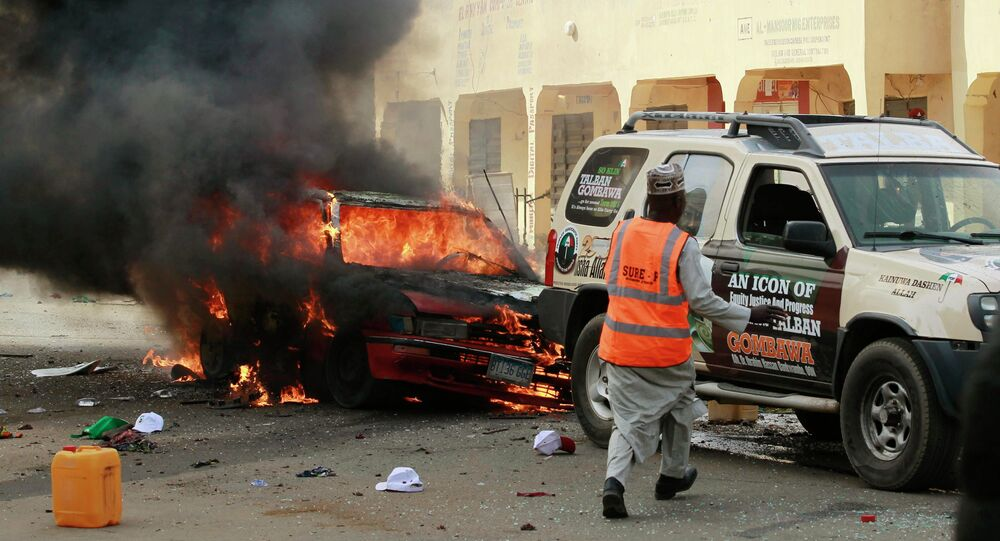 A man rushes towards a vehicle next to a burning car at the scene of a bomb explosion in Gombe
