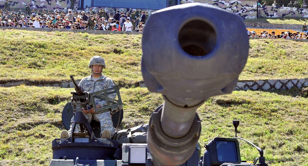 A US soldier sits on the top of M109A6 Paladin 155mm Howitzer