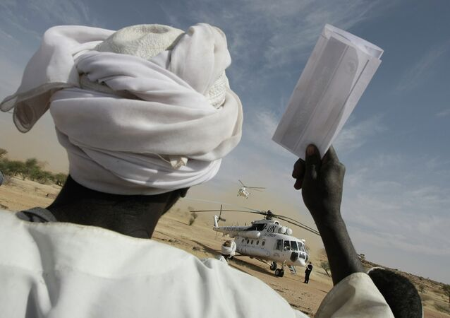 A Darfurian man chants slogans in favour of the Sudan Liberation Army (SLA) Wahid-Nur faction 17 January, as a United Nations helicopter lands in the area of Mulagat in northern Darfur