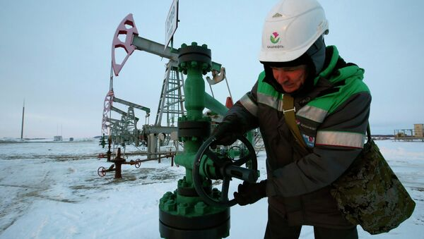 A worker checks the valve of an oil pipe at an oil field owned by Bashneft company near the village of Nikolo-Berezovka, northwest from Ufa, Bashkortostan, January 28, 2015 - Sputnik International