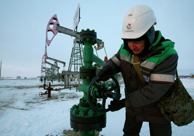 A worker checks the valve of an oil pipe at an oil field owned by Bashneft company near the village of Nikolo-Berezovka, northwest from Ufa, Bashkortostan, January 28, 2015