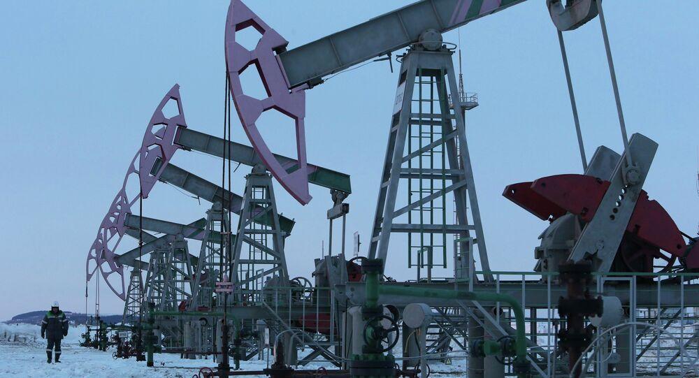 A worker walks past pump jacks on an oil field owned by Bashneft company near the village of Nikolo-Berezovka, northwest from Ufa, Bashkortostan, January 28, 2015
