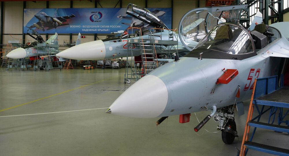 A Yak-130 combat-capable trainer aircraft, right, and Su-30MK multi-mission fighters in an assembly workshop at the Irkutsk Aviation Plant