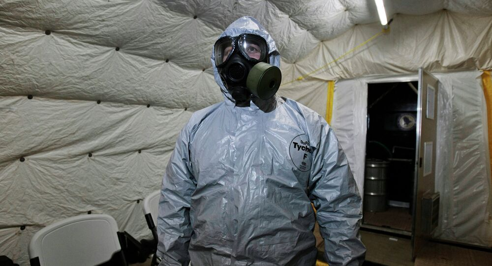A marine officer of the Cape Ray, a ship equipped to neutralize Syrian chemicals, shows a chemical protection suit to reporters