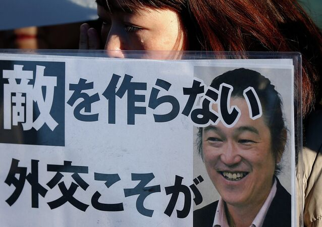 A woman cries as she holds a portrait of Japanese journalist Kenji Goto on a placard, during a rally against Japan's Prime Minister Shinzo Abe, in front of Abe's official residence in Tokyo