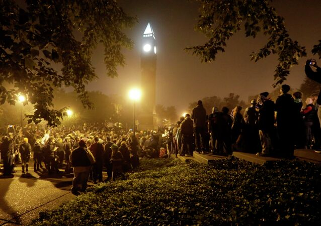 Protesters gather around the St. Louis University campus clock tower after a march through the streets of St. Louis, protesting against the recent shootings of two young black men by law enforcement officers, early Monday, Oct. 13, 2014.