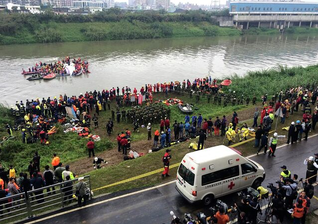 An ambulance arrives as rescuers carry out rescue operations after a TransAsia plane crashed into a river in New Taipei City, February 4, 2015.