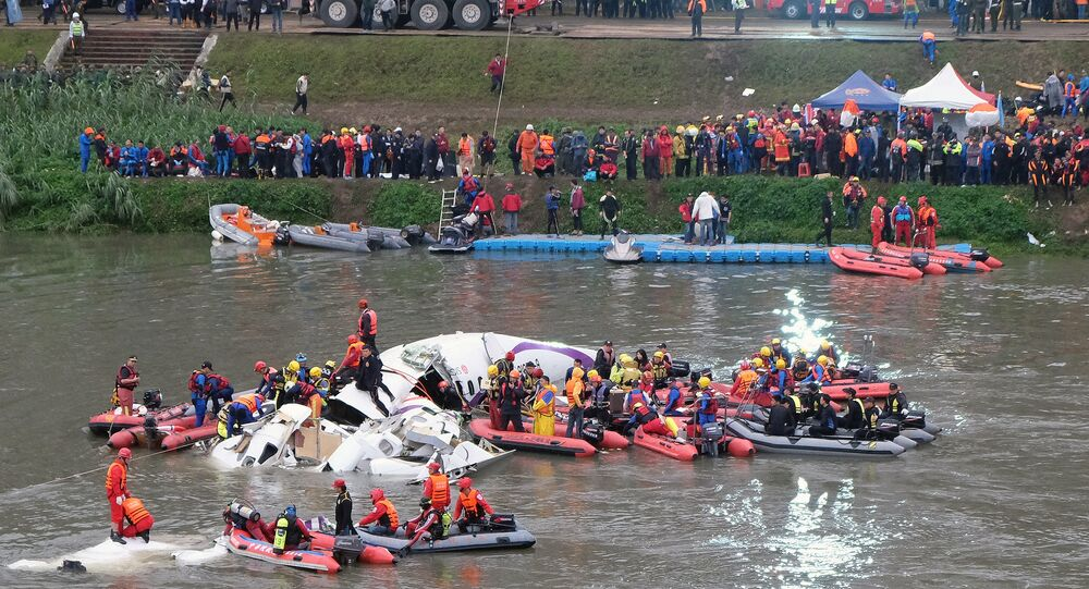 Rescue personnel search for passengers from the wreckage of a TransAsia ATR 72-600 turboprop plane that crash-landed into the Keelung river outside Taiwan's capital Taipei in New Taipei City on February 4, 2015.