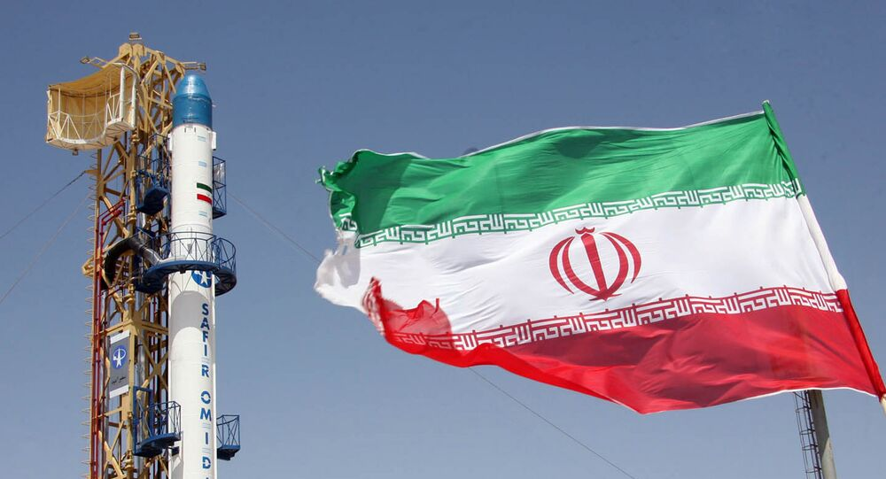 Iranian flag fluttering in front of Iran's Safir Omid rocket, which is capable of carrying a satellite into orbit, before it's launch in a space station at an undisclosed location in the Islamic republic