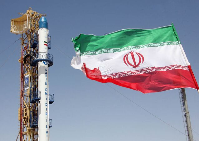 Iranian flag fluttering in front of Iran's Safir Omid rocket, which is capable of carrying a satellite into orbit. File photo