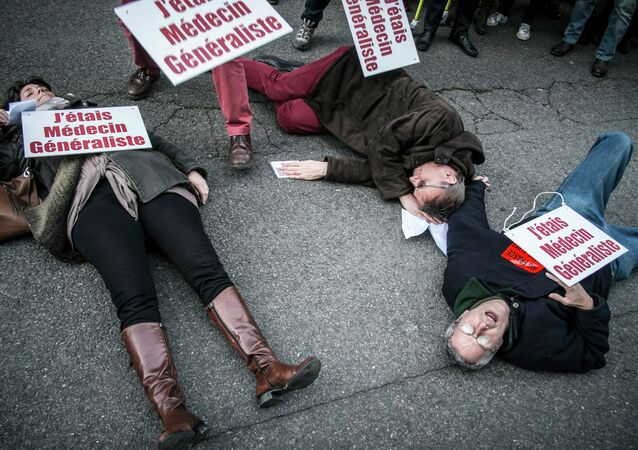 French doctors lie on the ground with a sign reading I was a health practitioner during a protest on December 23, 2014 in Lyon against an upcoming health bill.
