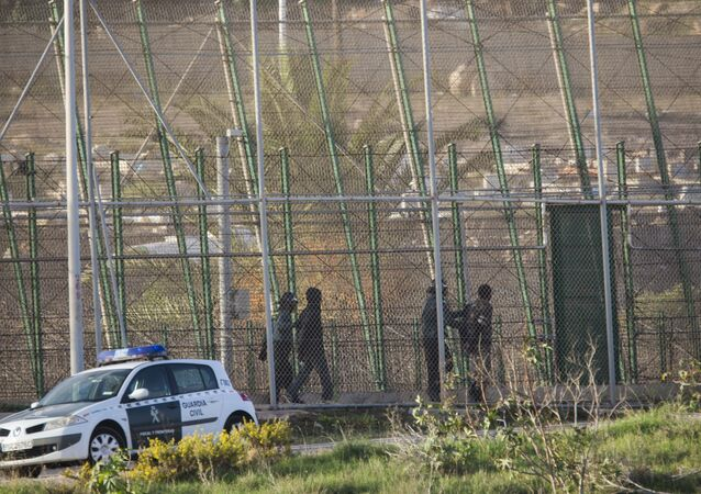 Sub-Saharan migrants are detained and sent back to the Moroccan side by Spanish Guardia Civil officers after scaling a metal fence that divides Morocco and the Spanish enclave of Melilla