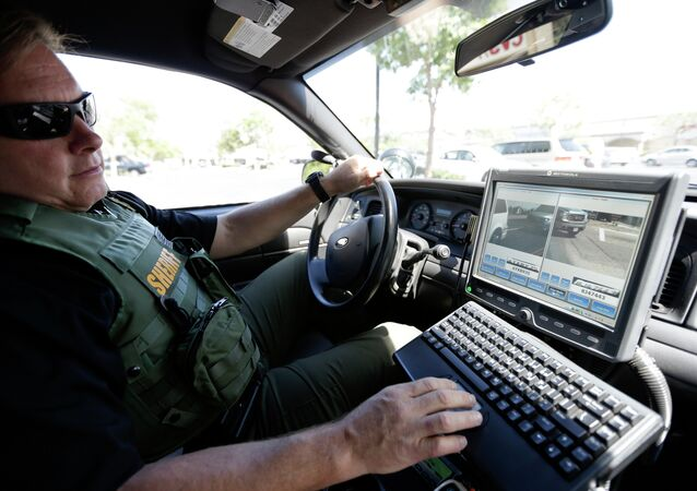 San Diego County Deputy Sheriff Ben Chassen looks at a monitor as his vehicle reads the license plates of cars in a parking lot.