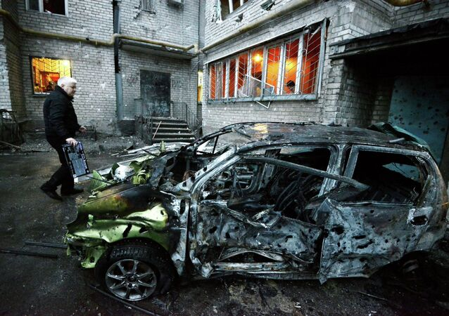 A man stands next to his car on Febuary 1, 2015 after it was destroyed by shelling today in the eastern Ukrainian city of Donetsk which is controlled by freedom fighters