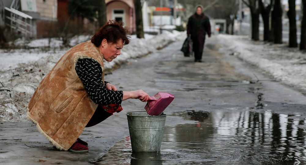 A woman gathers water in Donetsk