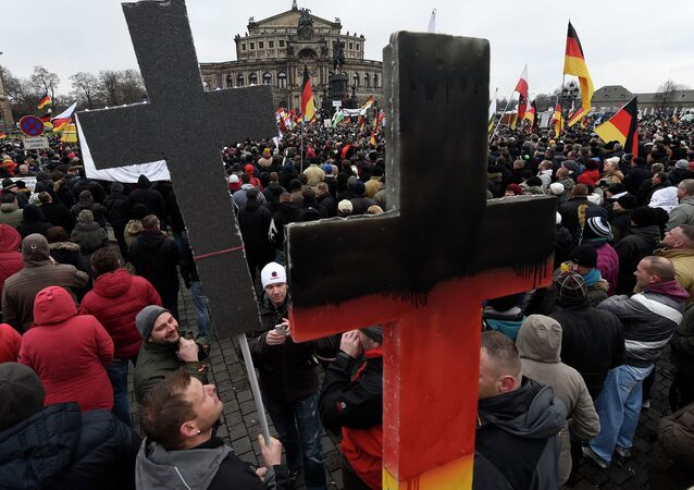 Demonstrators show crosses during a rally of the group Patriotic Europeans against the Islamisation of the West, or PEGIDA