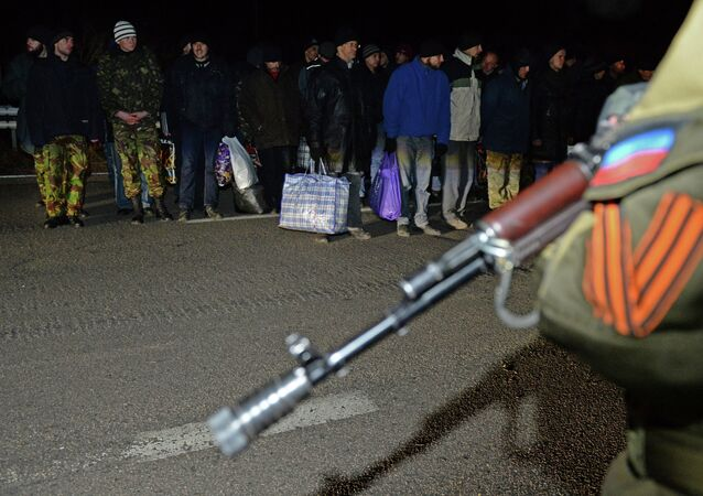 Ukrainian prisoners stand as a militant of the self-proclaimed People's Republic of Donetsk stands guard during a prisoner exchange with Ukraine on December 26, 2014