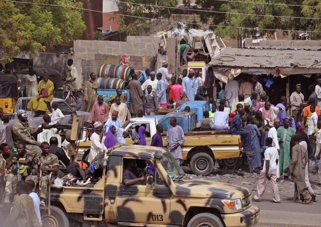 In this file photo taken Tuesday, Jan. 27, 2015, Nigerian Soldiers, left, pass by on the back of a armed truck as they patrol at a local market after recent violence in surrounding areas at Maiduguri, Nigeria