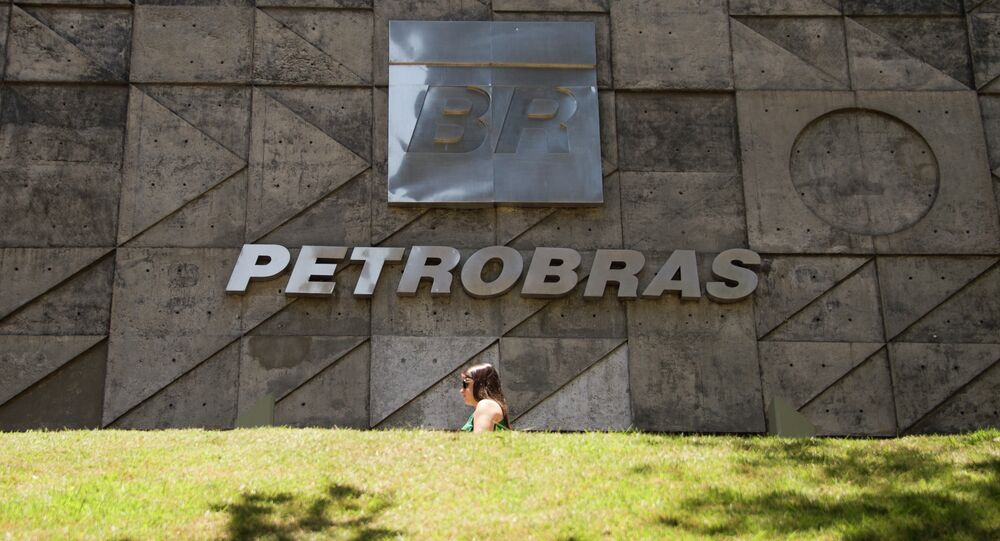 People walk past Petrobras building in Rio de Janeiro, Brazil on December 12, 2014