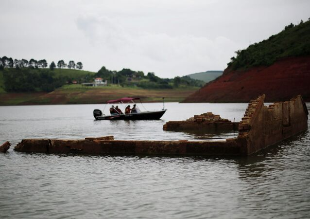 Tourists drive a boat past the walls of the old school of the re-emerging old city of Igarata in the Jaguari reservoir, Sao Paulo State, February 4, 2015