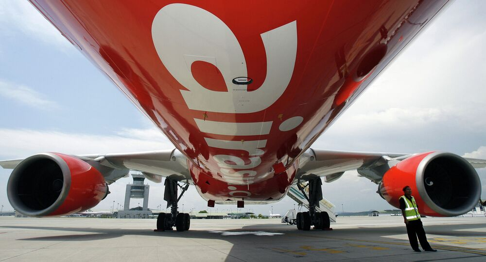 A security officer (R) stands by AirAsia X's first leased Airbus A330 long-haul aircraft as it sits on the tarmac of the Kuala Lumpur International Airport. File photo.