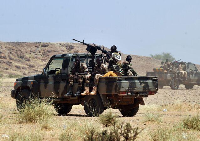Nigerien army patrolmen ride on vehicles in Ingall, northern Niger, on September 25, 2010