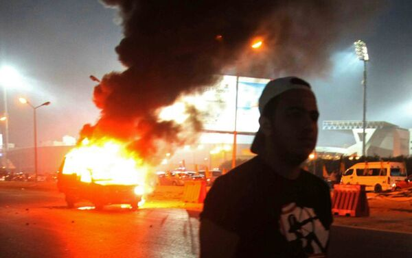 A soccer fan is seen near a police car, which was set on fire by fireworks, during clashes between soccer fans and security forces in front of a stadium on the outskirts of Cairo February 8, 2015 - Sputnik International