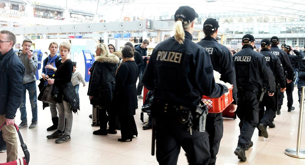 Police officers pass a row of waiting passengers during a strike of security employees at the airport Fuhlsbuettel in Hamburg, February 9, 2015