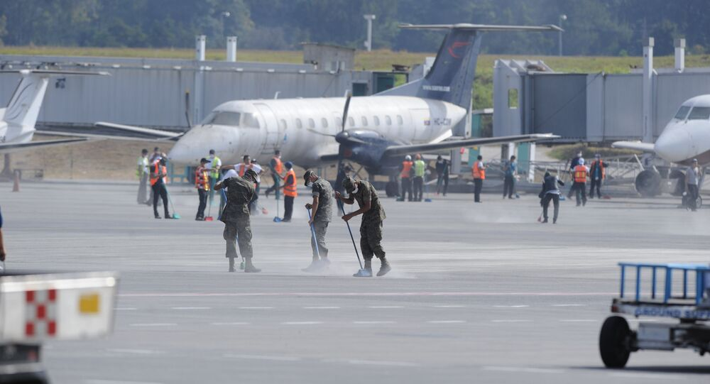 Members of Guatemalan Army clean ashes off of the runway of the La Aurora international airport, reported to be temporarily closed, in Guatemala City on February 8, 2015