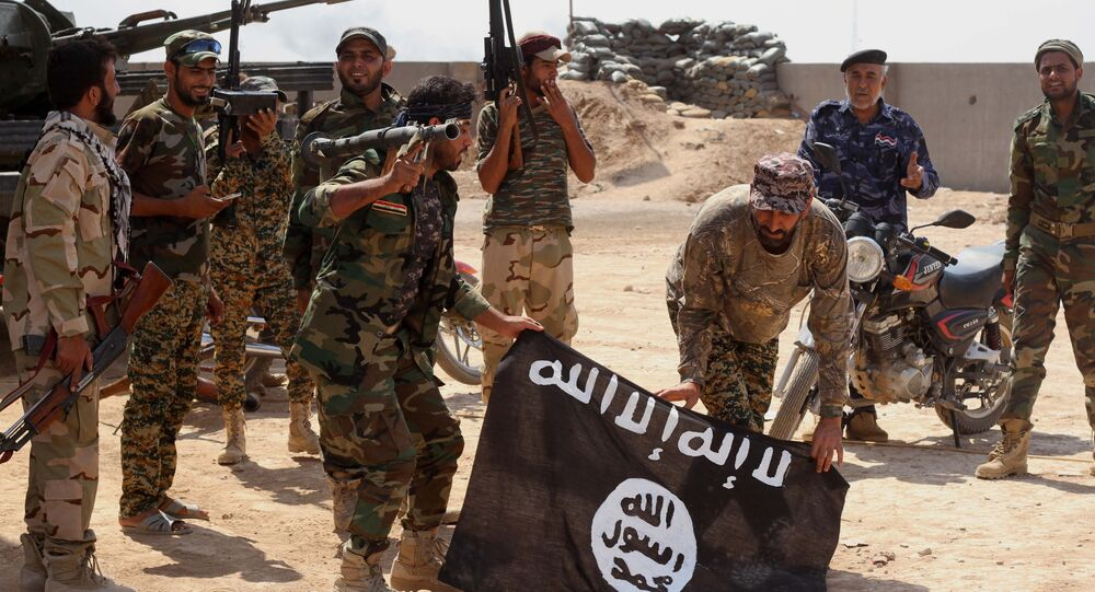 Iraqi security forces hold a captured ISIL flag in October, 2014.