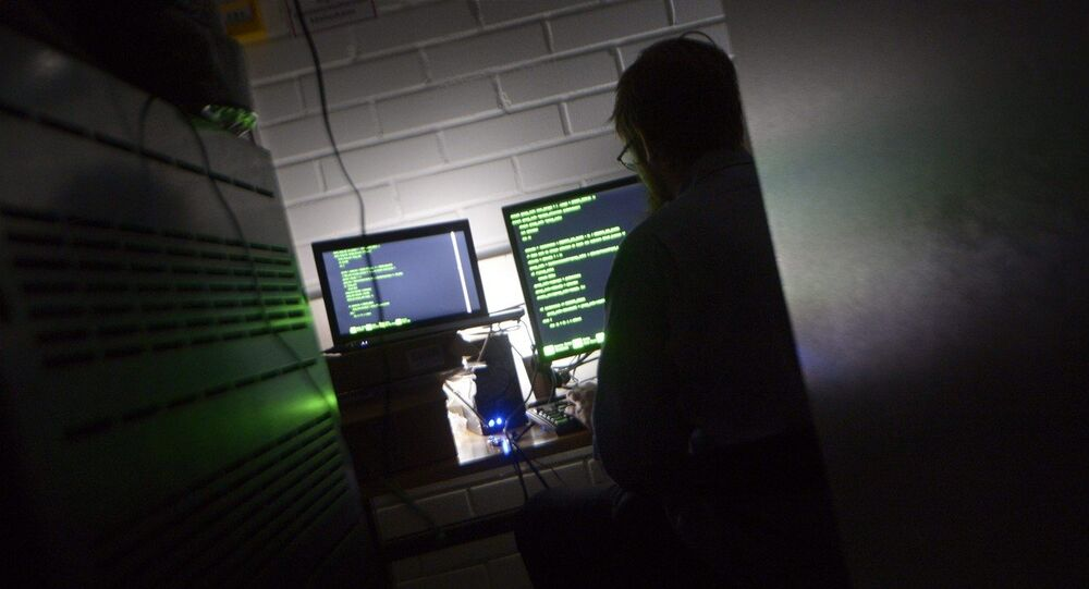 A man types on a keyboard in a computer server room
