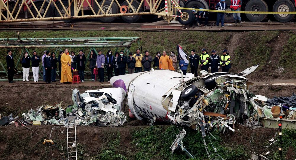 Relatives of the victims pray during a Buddhist ritual near the wreckage of TransAsia Airways plane Flight GE235 after it crash landed into a river