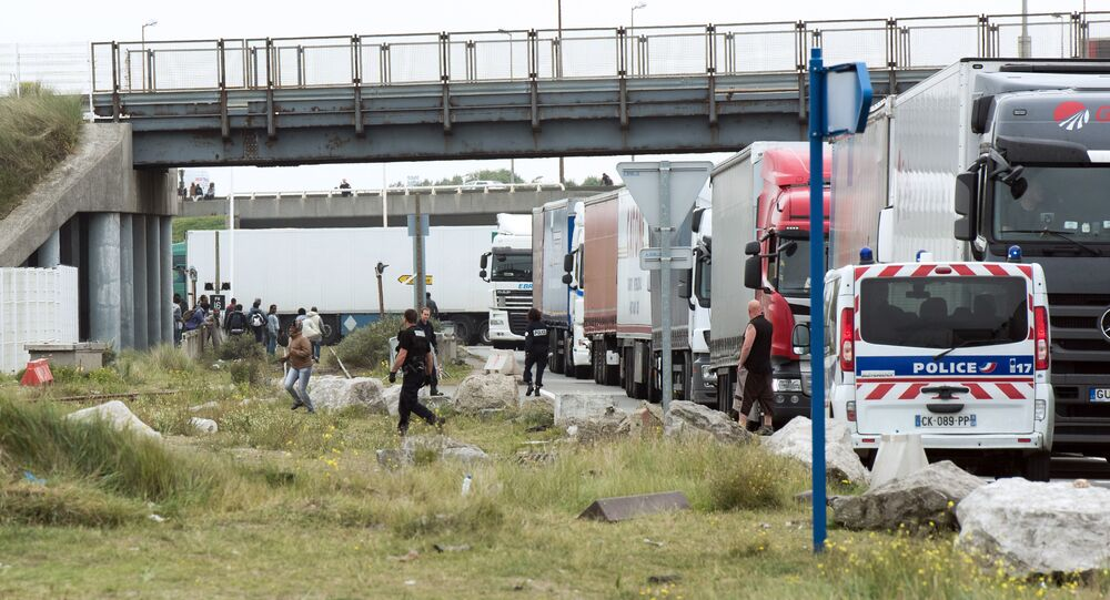 Policemen stand guard next to truck queuing to board a ferry to Great Britain to prevent migrants to reach the UK illegally