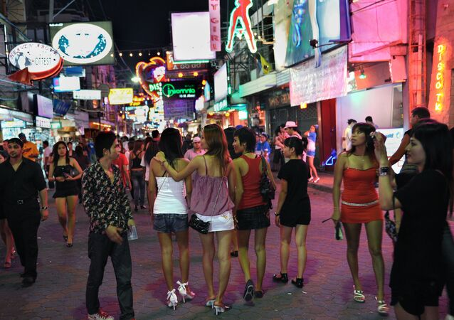 Men and women walk in the red light district in Pattaya, Thailand