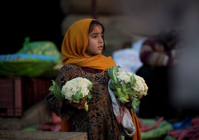 A Pakistani girl, who is displaced with her family from a Pakistani tribal area due to security forces' operations against militants, waits for customers to buy cauliflower at a fruit and vegetable market in Islamabad, Pakistan, Monday, Feb. 9, 2015.