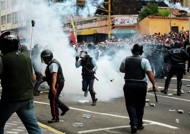 Police runs amidst tear gas as they clash with opposition students during a march against President Nicolas Maduro's government in San Cristobal February 12, 2015.