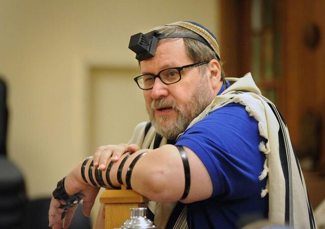 Rabbi Barry Freundel wears tefillin. Judaism teaches that the leather straps and boxes, which hold scriptural passages, are a way of connecting one's heart, head and hand in prayer.